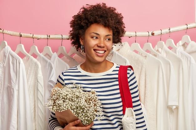 Concetto di persone, moda e consumismo. felice donna etnica distoglie lo sguardo, vestita in maglione a righe, porta bouquet e borsa