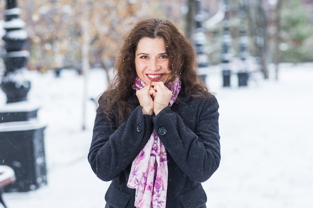 People, fashion and season concept - beautiful happy smiling young woman posing on winter snowy
