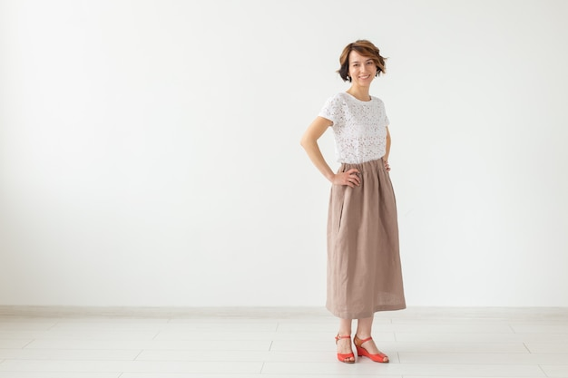People, fashion and style concept - young woman posing in clothes in studio on white wall.
