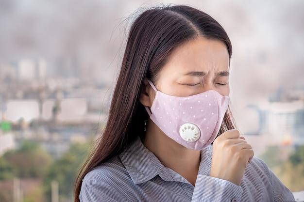 대기 오염으로 아픈 사람들은 환경에 유해하거나 유독 한 영향을 미칩니다. 자신을 보호하기 위해 얼굴 마스크를 쓰고 도시의 여자