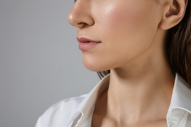 人、女性らしさ、美しさ、スタイル、ファッションのコンセプト。白いシルクのフォーマルシャツを着て、空白のコピースペースの壁にポーズをとって光沢のある肌とピンクの唇を持つ未知の女性のトリミングされた写真