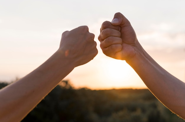 People fist bumping at the sunset