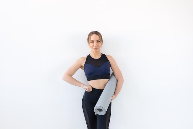 人、フィットネス、スポーツのコンセプト。白い背景の上に灰色のマットを保持している魅力的で健康な女性