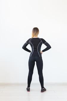 Люди, фитнес и спортивная концепция - вид стоя молодой спортивной женщины на белом фоне сзади.