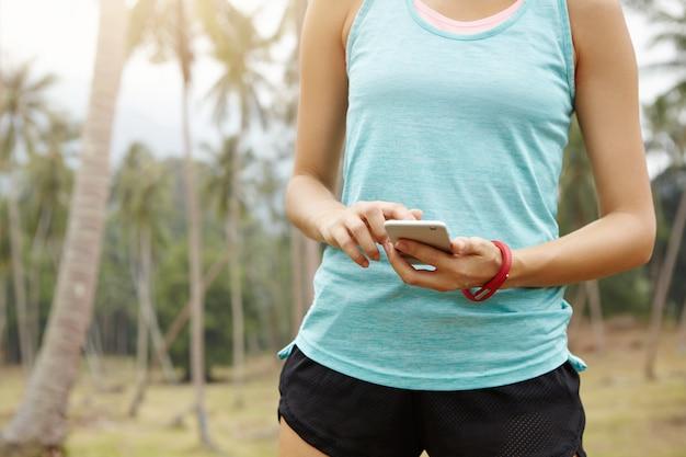 人、フィットネス、テクノロジーのコンセプト。携帯電話を使用してスポーツウェアの女性ランナーの中央部、彼女の進行状況を監視するためのアプリの設定を確認します。