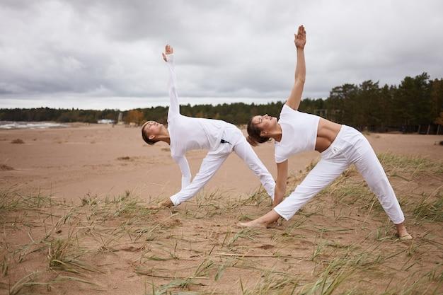 사람, 피트니스, 스포츠, 우정, 가족 및 라이프 스타일 개념. 전문 여성 요가 강사와 십대 아들 모두 흰 옷을 입고 맨발로 모래 위에 서서 utthita trikonasana를하고 있습니다.