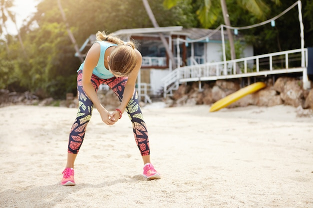 People, fitness, sports and healthy lifestyle. young female athlete wearing colorful leggings and sneakers standing on sand, leaning over and resting her elbows on her knees, relaxing after workout