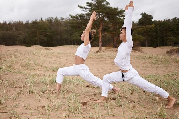 사람, 피트니스, 요가, 필라테스 및 활동적인 건강한 라이프 스타일 개념. virabhadrasana 또는 전사 1을하고 흰색 옷을 입고 스포츠 맨발 젊은 백인 남자와 여자의 여름 촬영 야외 포즈