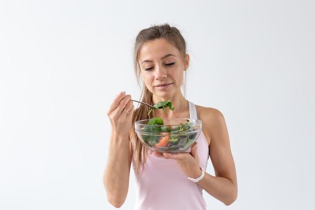 人、食べ物、ダイエットのコンセプト。白い背景の上に健康的な食べ物を食べる女性の肖像画。