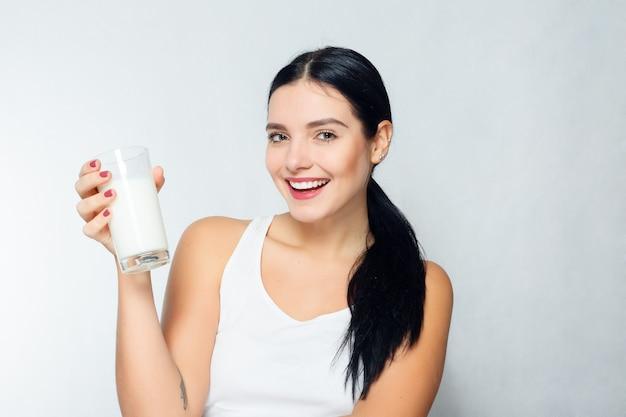 Люди, еда, красота, образ жизни, мода и деликатная концепция - молоко - женщина пьет молоко, счастливая и улыбающаяся красивая молодая женщина, наслаждающаяся стаканом молока