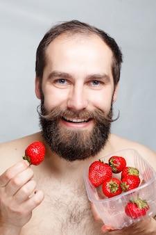 사람, 음식, 아름다움, 라이프 스타일, 발렌타인 데이 개념 - 클로즈업 초상화 젊은 남자가 딸기를 들고 웃고 있습니다. 잘생긴 수염과 콧수염의 초상화입니다. 회색 배경에