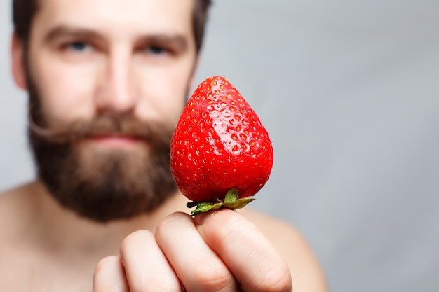 People, food, beauty, lifestyle, valentines day concept -close-up portrait young man holding a strawberry and smiling. portrait of handsome bearded and mustache. on a gray background