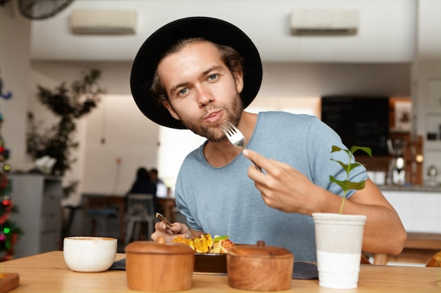People, food and lifestyle concept. indoor shot of attractive young student wearing black hat and blue t-shirt appeasing his hunger