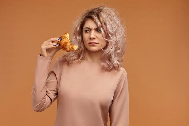 人、食べ物、ペストリー、甘い焼き菓子、ダイエットのコンセプト。彼女の手でクロワッサンを見つめているピンクがかった髪の眉をひそめている欲求不満の若いヨーロッパの女性のショット
