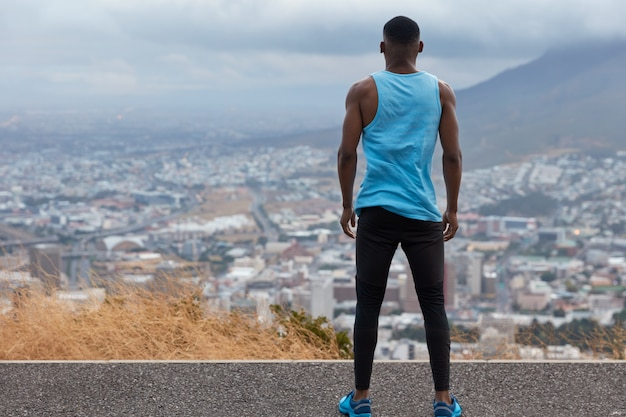 People, freedom, lifestyle concept. back view of sporty man in sportsclothes, stands high on road, looks from above on wonderful city view with skycrapers, blue sky and volcano, trains sport outside
