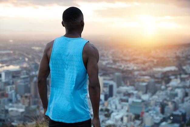 사람, 자유, 여가 시간 개념. 캐주얼 한 파란색 조끼를 입은 편안한 남성 트레이너는 시골에서 차분한 분위기를 즐기고, 꼭대기에 서고, 멀리서 대도시를 바라보고, 새벽을 기다립니다, 아침 운동을합니다.