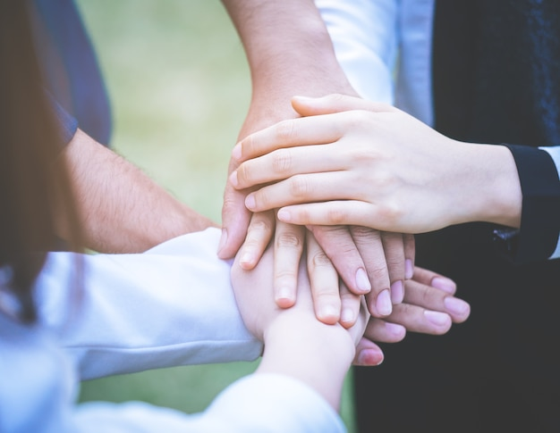 Друзья друзей товарища по команде, кладя руку вместе для концепции команды