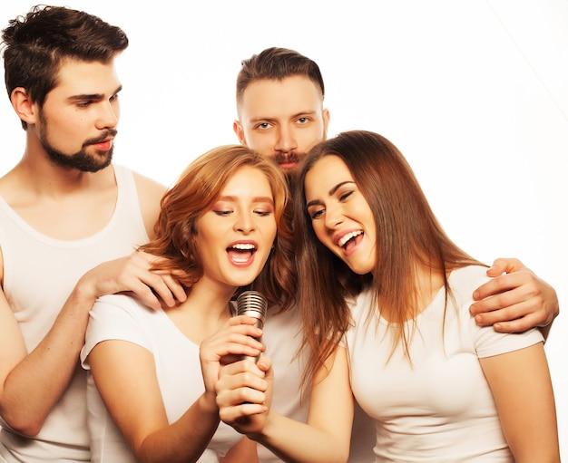 人、友情、レジャーのコンセプト:カラオケ、流行に敏感なスタイルで楽しんでいる若い幸せな友人のグループ。白で隔離。