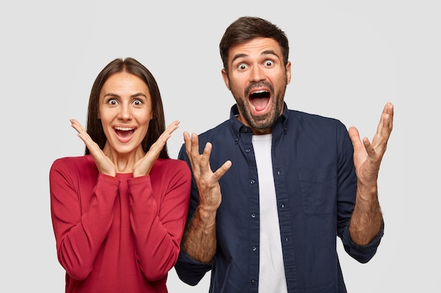 People, friendship and happiness concept. happy joyful young caucasian woman and man excaim loudly