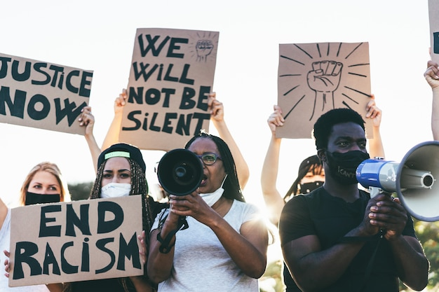 People from different ages and races protest on the street for equal rights - demonstrators wearing face masks during black lives matter fight campaign -