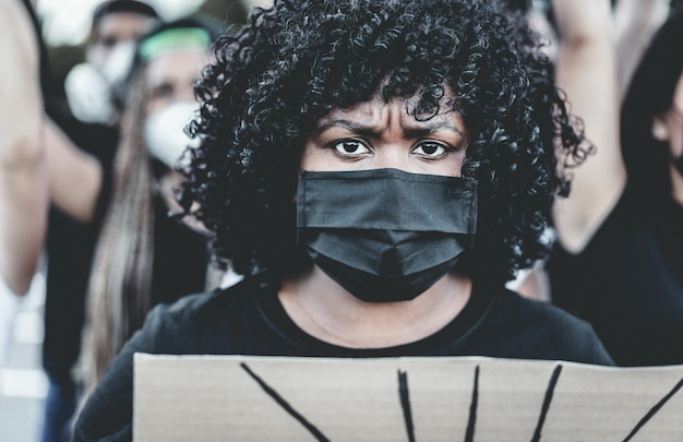 People from different culture and races protest on the street for equal rights - demonstrators wearing face masks during black lives matter fight campaign - main focus on mask