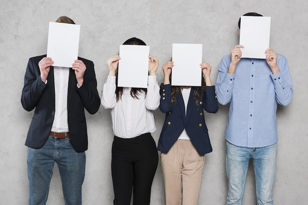 People from human resources holding up blank papers Premium Photo
