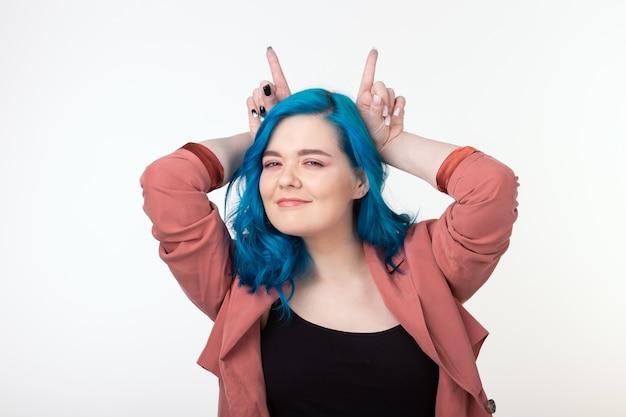 Люди, веселье и концепция волос - красивая девушка с синими волосами, весело стоя на белой стене.