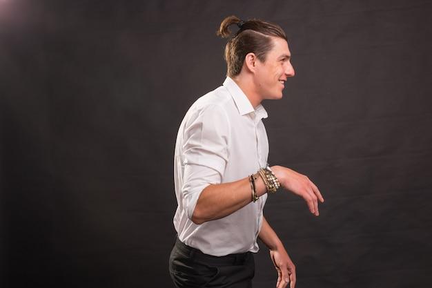 人々、楽しさとスタイルのコンセプト-茶色の壁に面白いヘアカットダンスをしているハンサムな男。