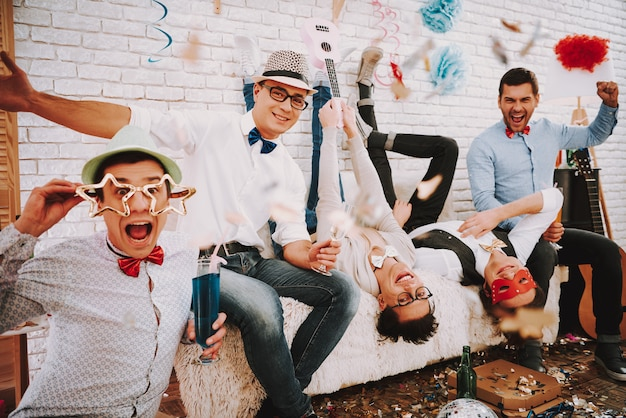People gay in bow ties playfully posing on couch at party