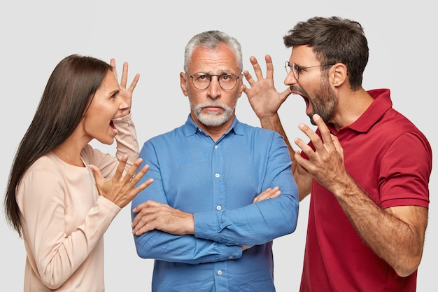 People, generation and relationships concept. angry female and male gesture and shout with madness at their senior father pensioner, sort out relations, live together in one flat, being annoyed