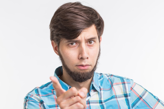 People, gesture and emotions concept - young man waving his finger on white background