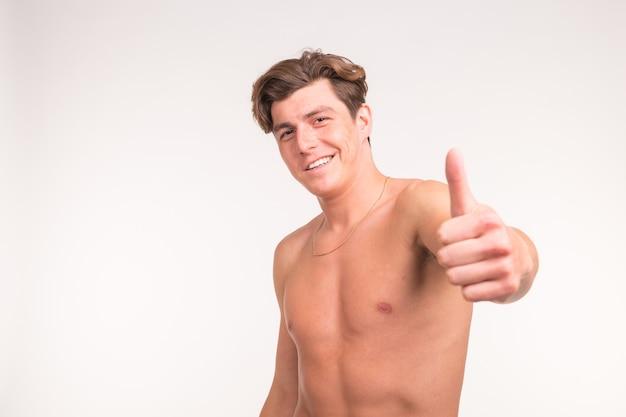 사람, 제스처, 피트니스 및 스포츠 개념-흰 벽에 엄지 손가락을 보여주는 운동 shirtless 남자.