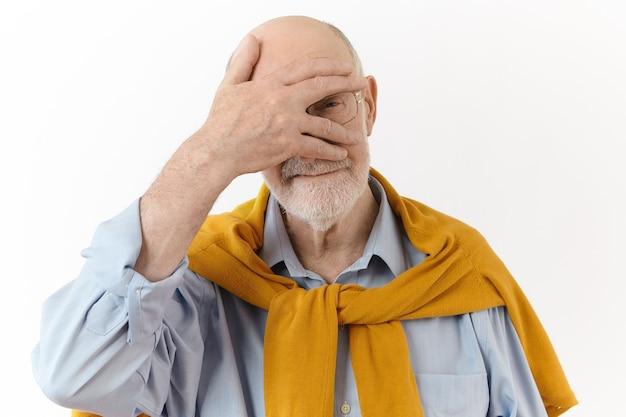 사람, 제스처 및 징후 개념. 세련된 백인 노인 형태가 이루어지지 않은 남성 안경과 우아한 옷을 입고 그의 얼굴에 손바닥을 유지하고 손가락을 통해 카메라를 엿보는 격리 된 포즈