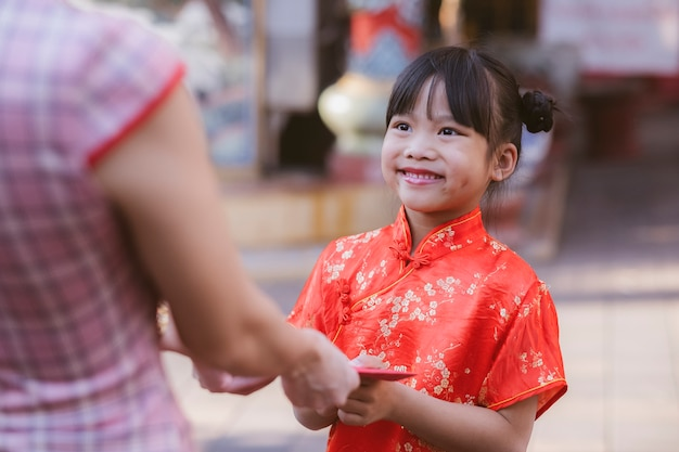 People giving red envelope (ang pao) to child.