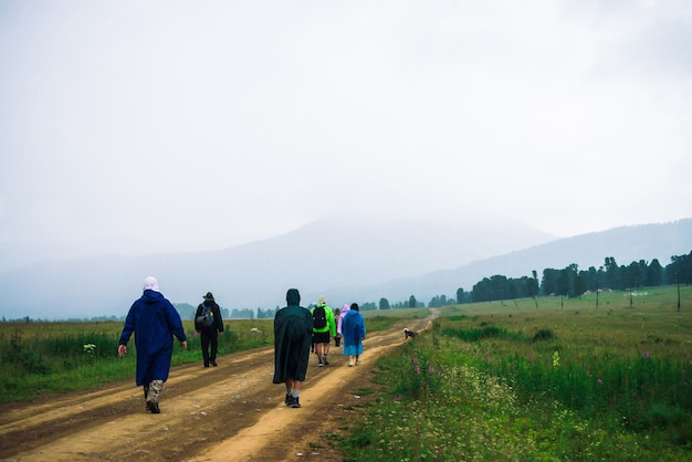 Люди идут вперед в гору, несмотря на непогоду. путешественники с собакой идут вверх по дороге