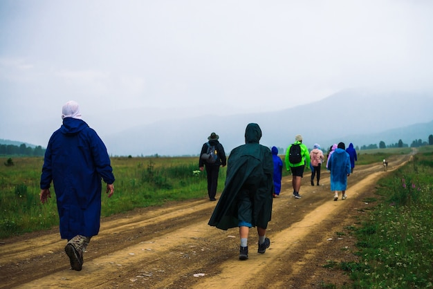 People go forward in mountain despite bad weather. travelers goes upwards along road after dog. way on foot in highlands in rainy overcast day.