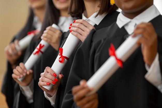 卒業証書のクローズアップで卒業する人々