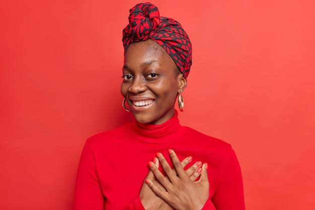사람들은 감사와 감사 개념입니다. 기뻐하는 아프리카계 미국인 여성이 하트에 손을 대고 부드러운 감정을 표현하며 칭찬에 감사한다고 말하며 뭔가를 감탄하고 있습니다.