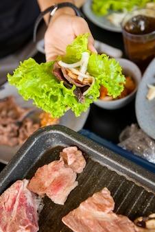 Люди готовят корейское барбекю в ресторане