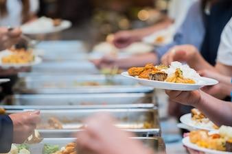肉のカラフルなフルーツとvegetablと豪華なレストランで屋内の人々のグループケータリングビュッフェ式の料理