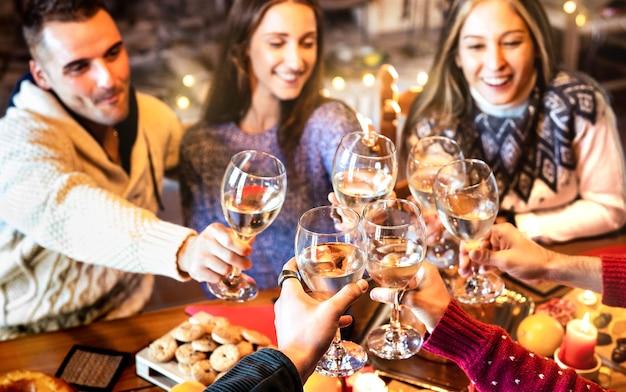Группа людей, празднующих рождество, поджаривая шампанское с вином на домашнем ужине - в центре внимания - очки