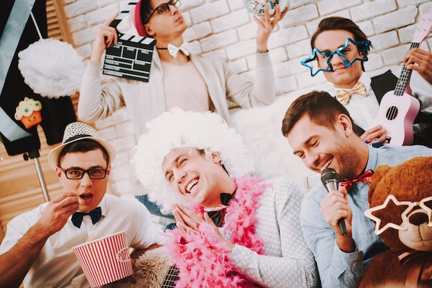 People guy in bow ties posing together on couch at party