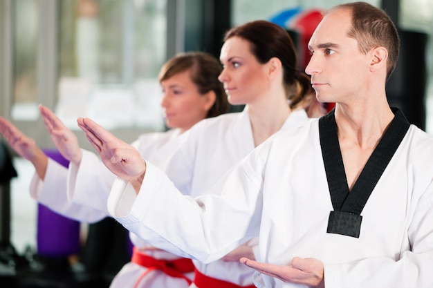 People in a gym in martial arts training exercising taekwondo