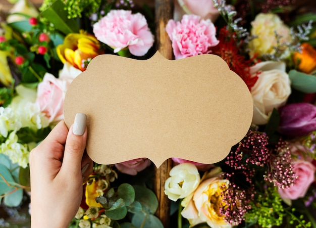 People hand holding blank design space card with flowers bouquet background