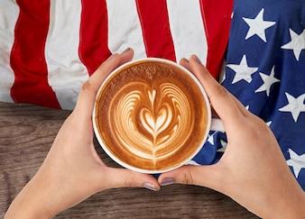 人々の手は7月4日とcoffeのカップを持って