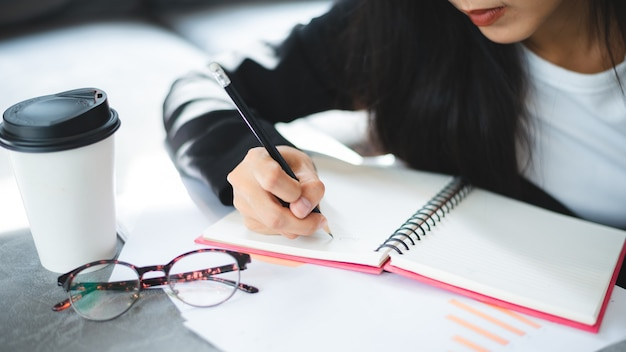 People hand holding a pen for working to write on a book for letter or business document, student education concept to learning by using notebook paper page to note a diary on a office table