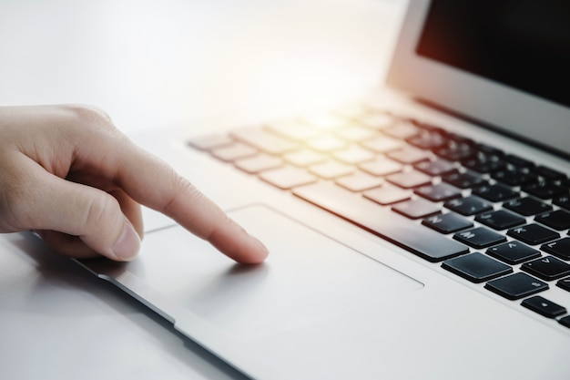 People hand touching touchpad on laptop computer on desk at home office, work from home, searching web, social network, online, business strategy, finance, investment and digital technology concept
