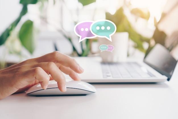 채팅 아이콘 팝업에서 노트북 입력, 채팅 또는 문자 메시지를 사용하는 사람들의 손. 기술 개념을 만드는 소셜 미디어. 빈티지 부드러운 색조 배경입니다.