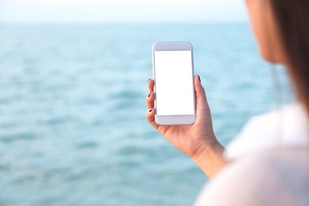 海でモックアップスマートフォンを使用して人々の手