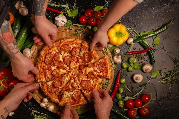 ペパロニピザを持っている人の手。黒いコンクリートの背景に食材トマトバジルを調理します。ホットペパロニピザの上面図。テキスト用のコピースペース付き。フラットレイ